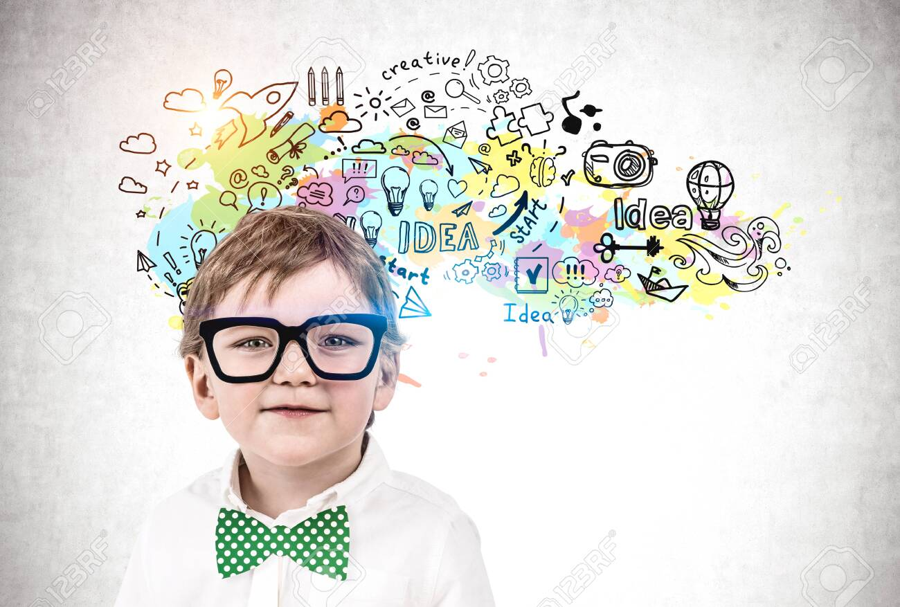 Adorable little boy in glasses and green bowtie standing near concrete wall with colorful creativity sketch drawn on it. Concept of development and education - 139803079