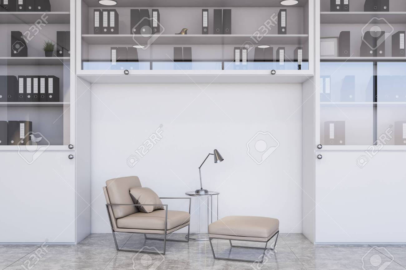Comfortable beige armchair standing in modern office lounge with white walls, concrete floor, white bookcase with folders and stylish lamp. 3d rendering - 141623403