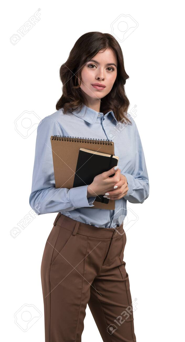 Isolated half length portrait of beautiful young businesswoman or college student with wavy dark hair holding notebooks. Concept of education and planning - 143497539