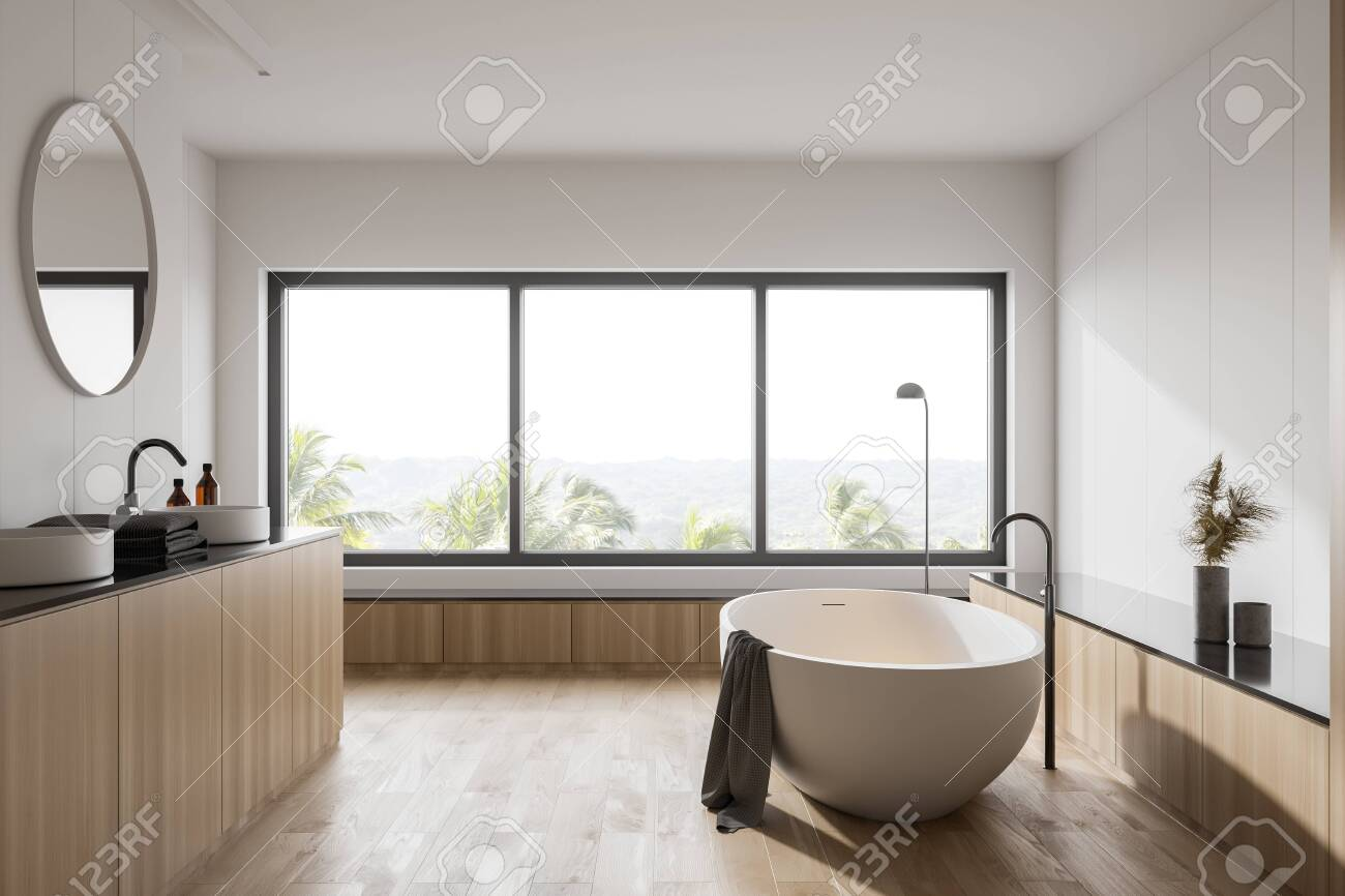 Interior of hotel bathroom with white and wooden walls, wooden floor, comfortable white bathtub and sink with round mirror. Window with blurry tropical view. 3d rendering - 144131393