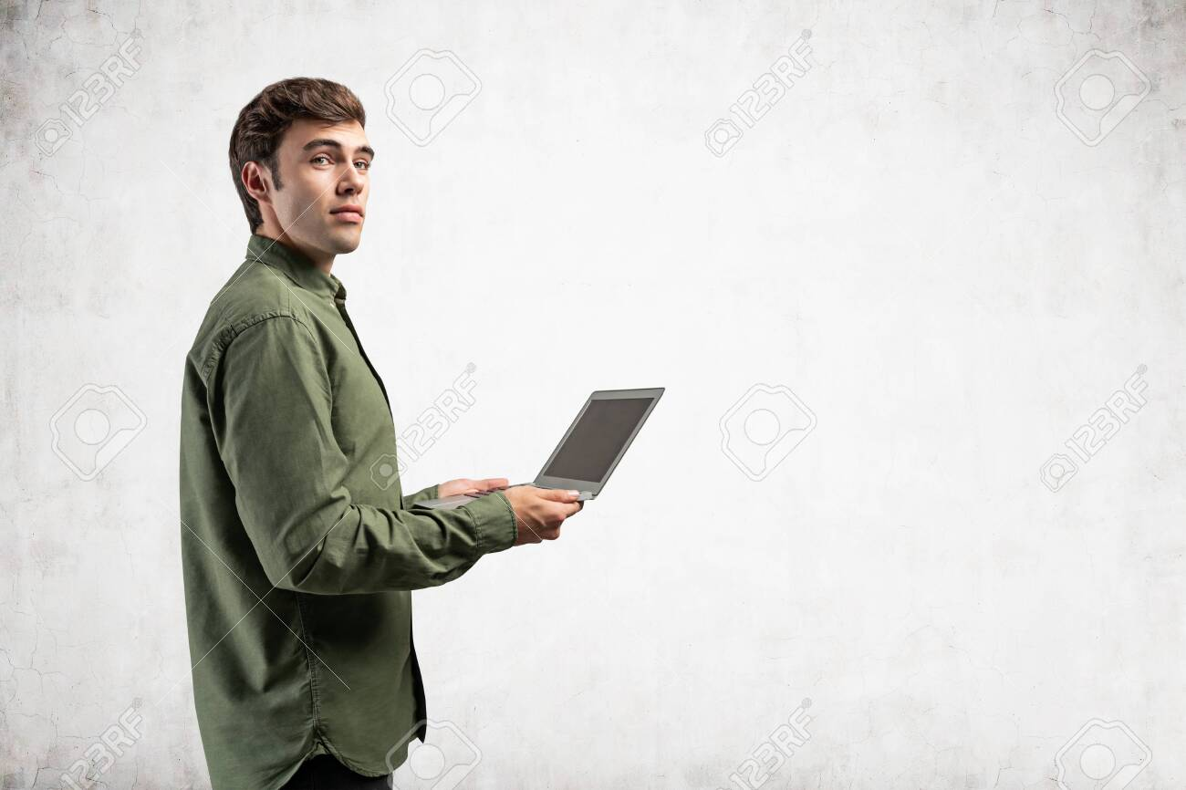Side portrait of inspired young college student or computer guy in green shirt holding laptop near concrete wall. Concept of internet, communication and education. Mock up - 145240999