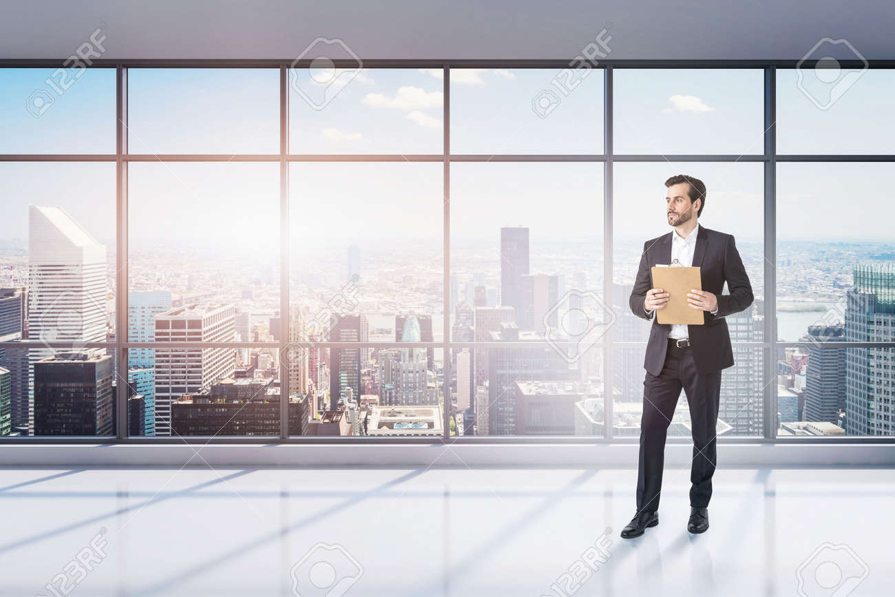 Portrait of young businessman with clipboard standing in empty panoramic office. Concept of paperwork and leadership. Toned image - 159794076