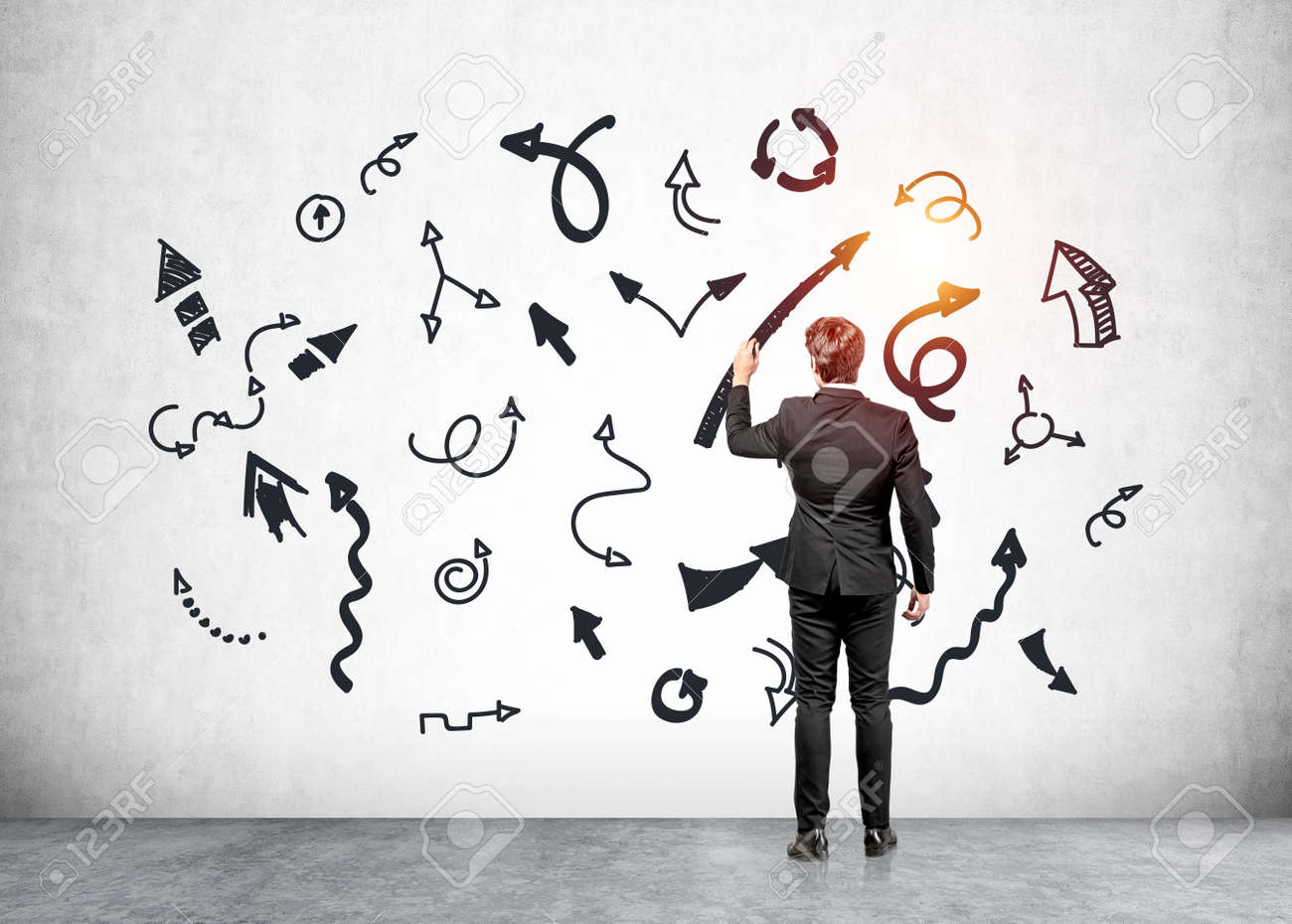 Office man in black suit holding pen, writing multiple lines and arrows with different direction, concrete floor. Concept of decision making and solution - 169807444