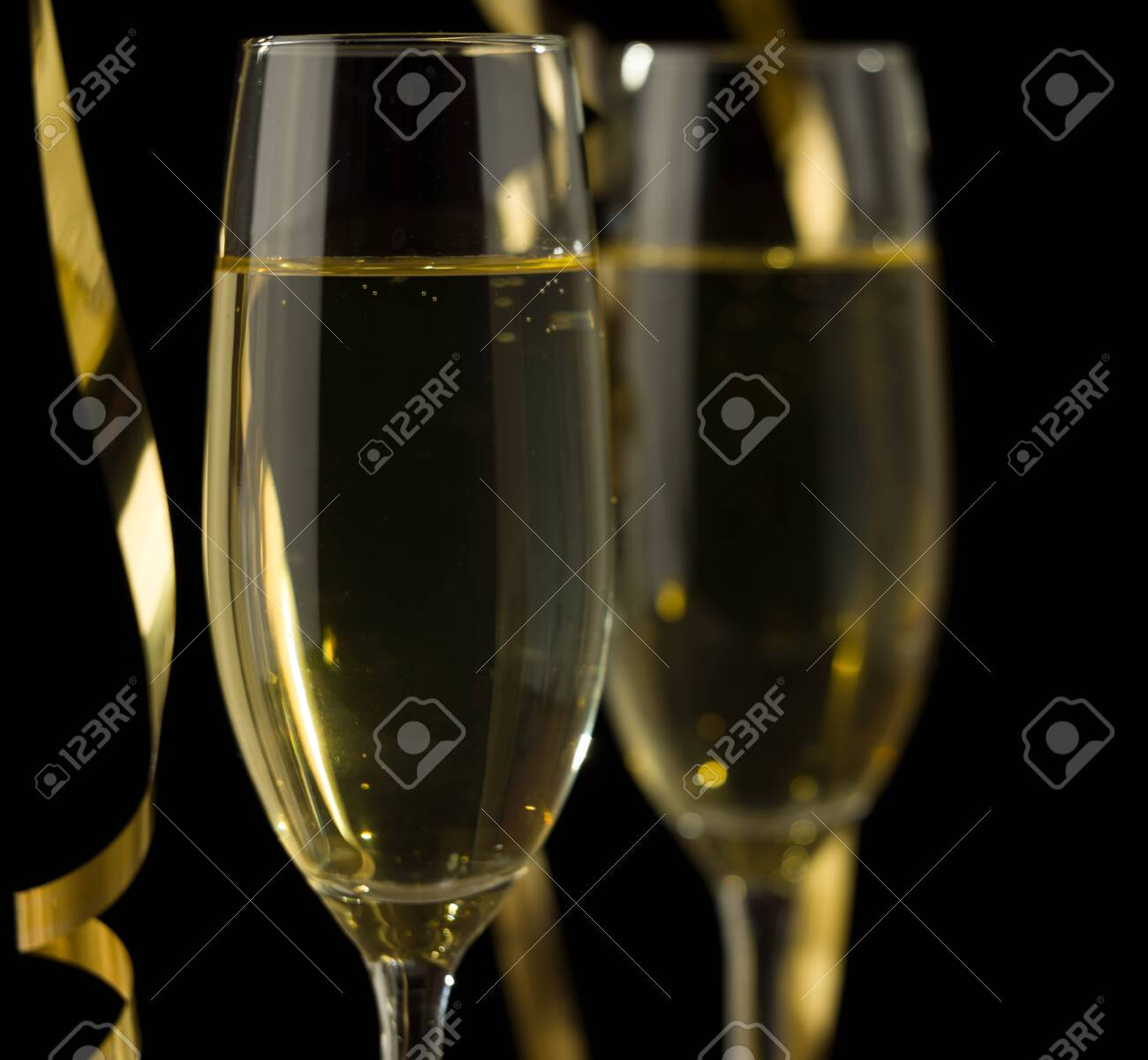 Two glasses of champagne in front of dark background - 137576570
