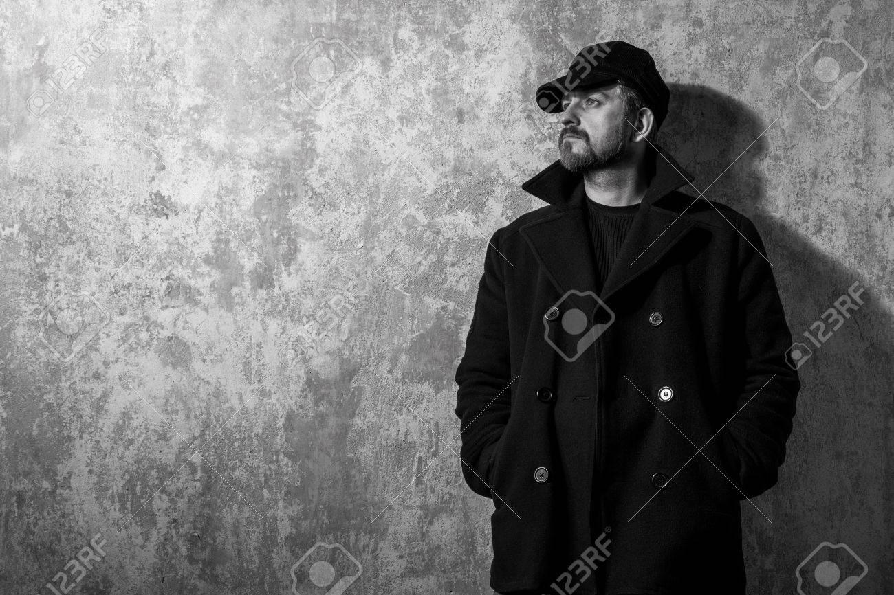 Casquette Photo Et Debout Homme Mur Cru Vieux Manteau Noir Près Du Bwq5za
