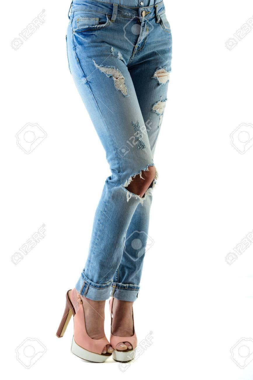 La donna in caldo tacchi alti rosa e jeans. primo piano di metà inferiore del corpo isolato su sfondo bianco.