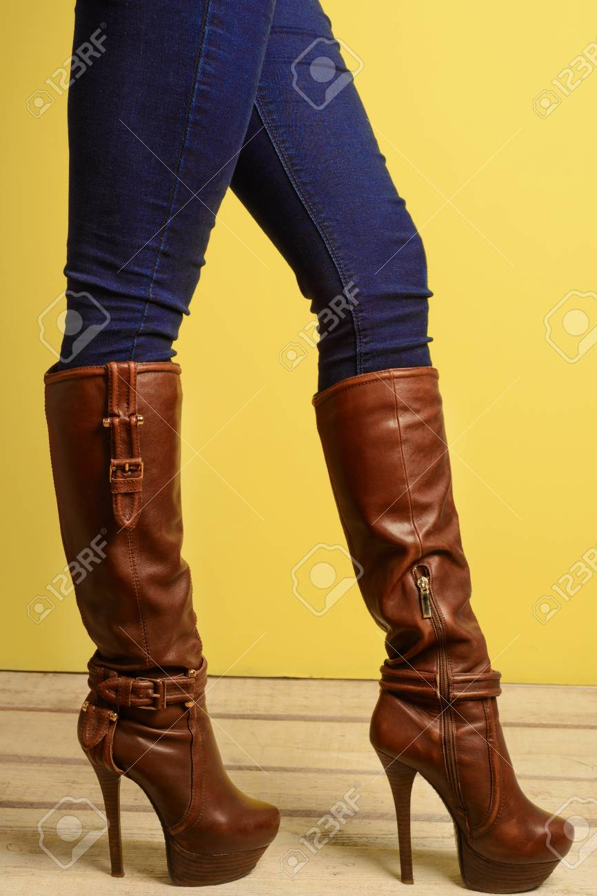 71efb0372c5a sporty girl standing in brown high-heeled boots and jeans Stock Photo -  91426061