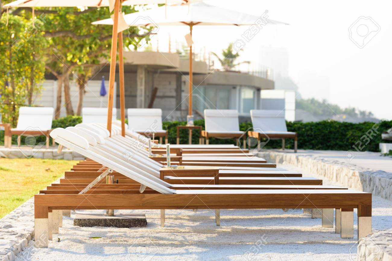Stock Photo - Sun beds and umbrellas at the poolside. & Sun Beds And Umbrellas At The Poolside. Stock Photo Picture And ...