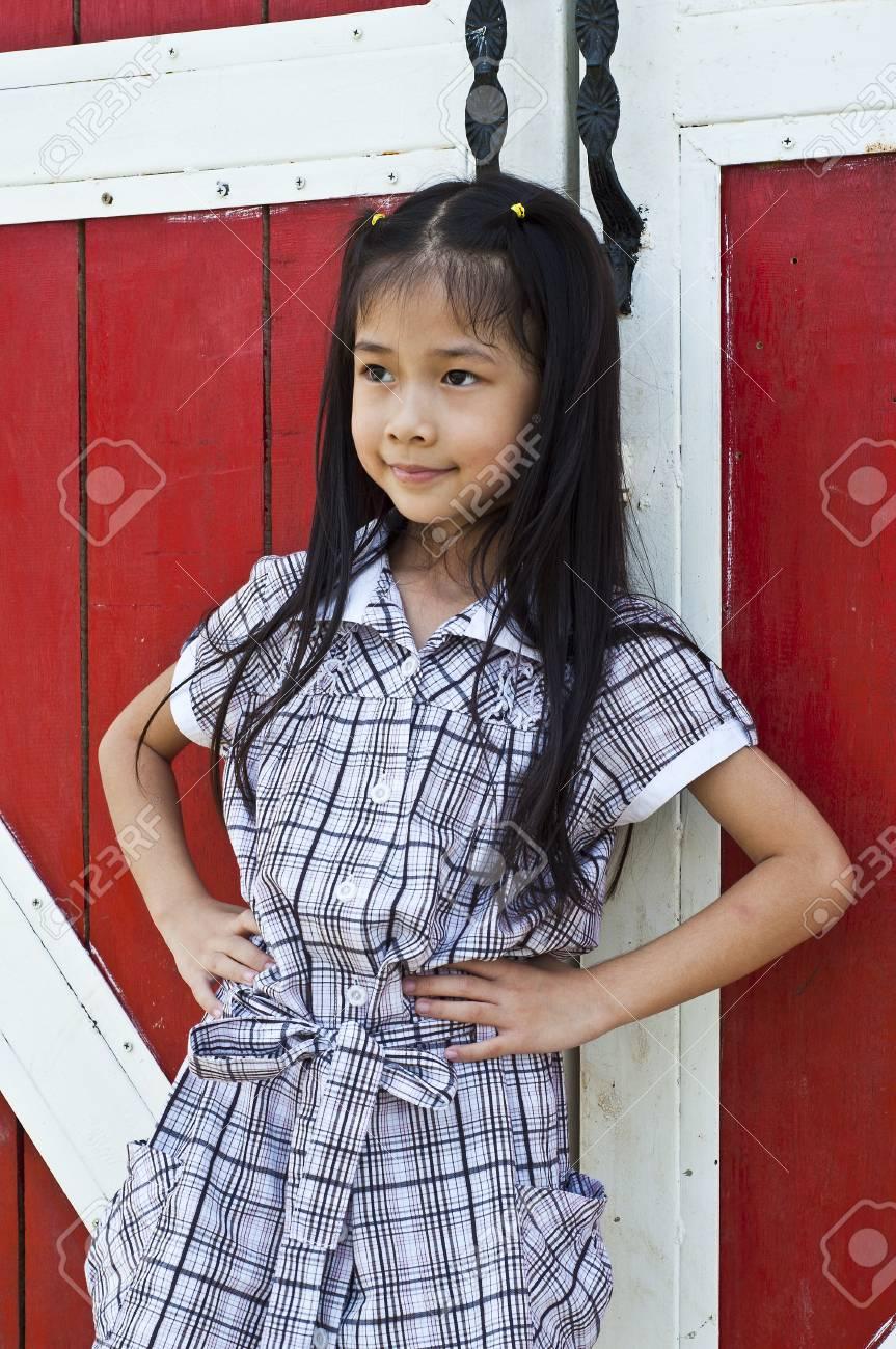 Little asian girl posing in front of red wooden door Stock Photo - 18448486