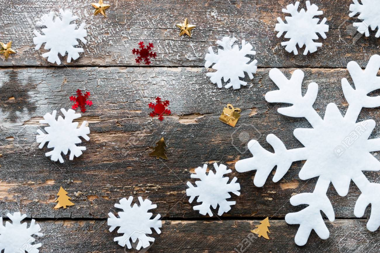 Large And Small Snowflakes On A Wooden Background
