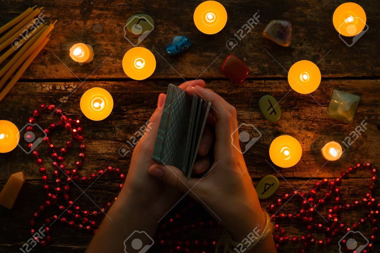 fortuneteller reads fortunes by tarot cards and candles on the background of the runes - 66320448