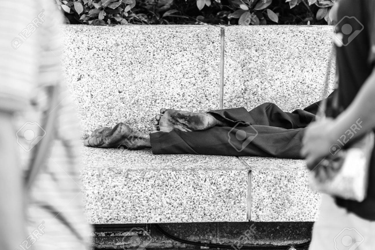Homeless people sleeping at streetside in city black and white