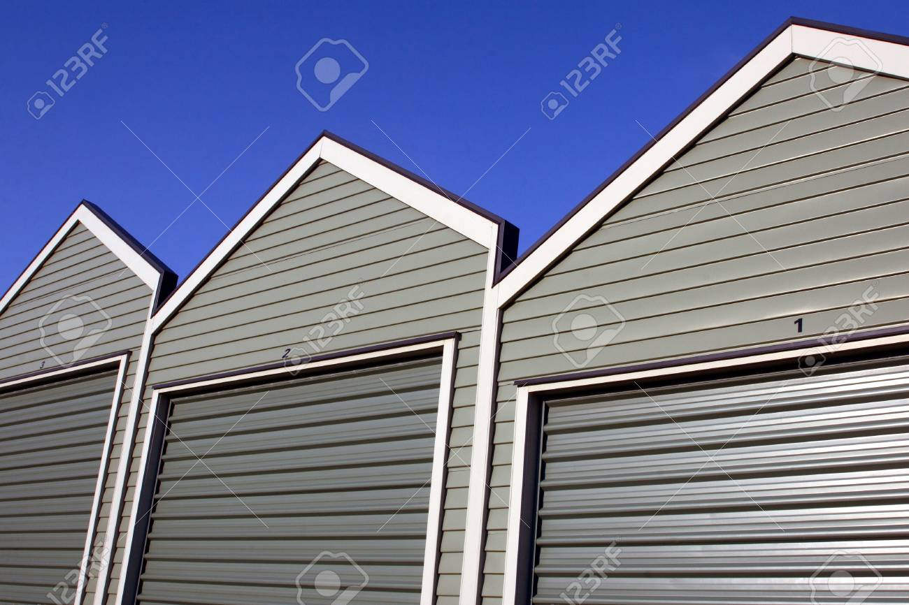 A row of uniform garages with roller doors on a blue sky background Stock Photo - 16578115