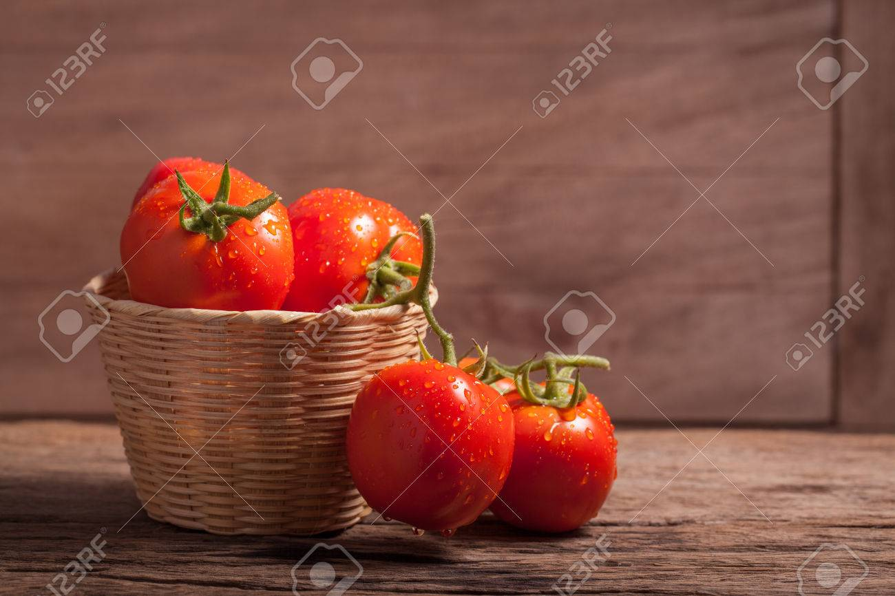 juicy red tomatoes in basket on wooden table - 35481737