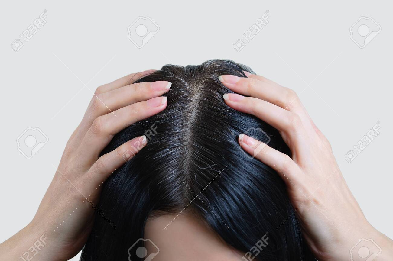 Head of a caucasian woman with black gray hair. Fingers in hair. - 135875553