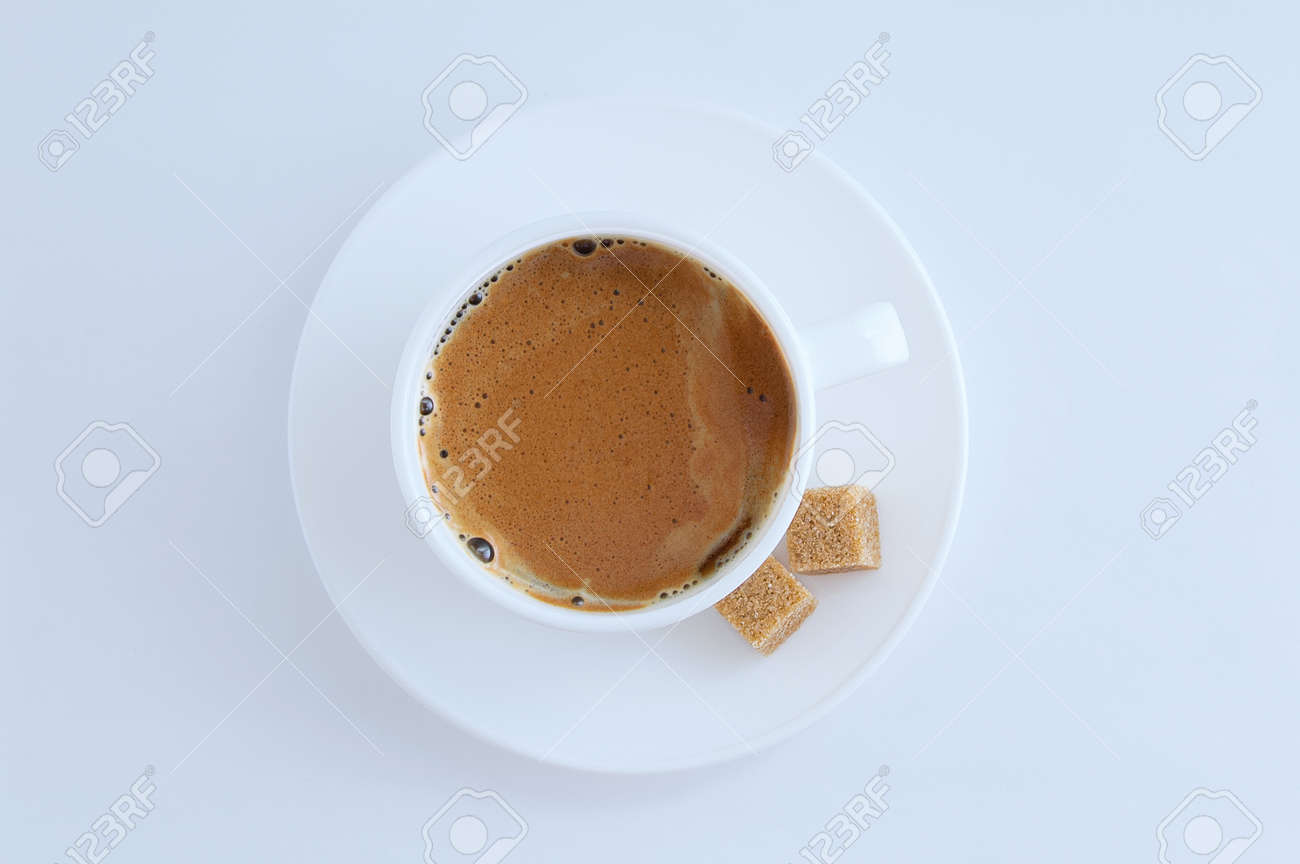 White cup of coffee with froth and cane sugar cubes on a saucer on a white background. - 166242037