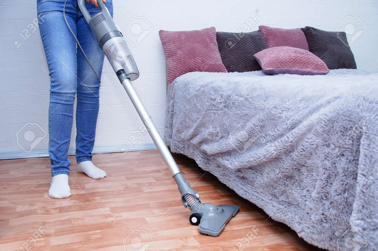Handheld gray vacuum cleaner in the hand of a Caucasian woman in jeans. Vacuum the floor in the room. - 166396150