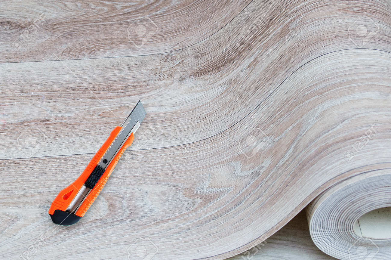 Unwound roll of beige linoleum with wood texture and construction knife for cutting. - 171076392