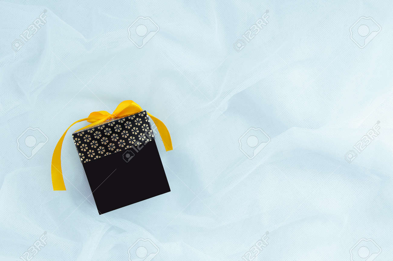Black gift box with a yellow bow on a white fabric background. Place for your text. - 171076361
