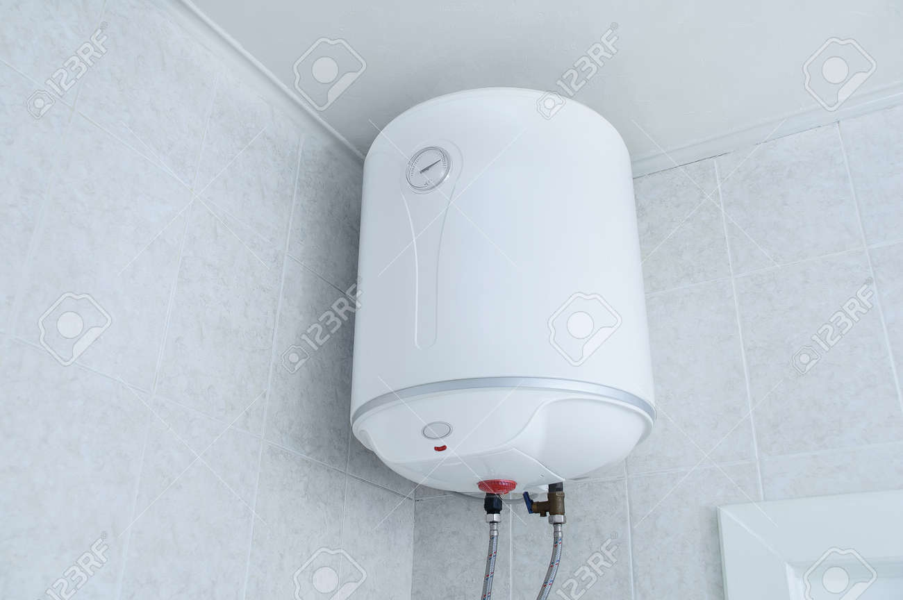 White electric water heater boiler on the wall in the bathroom. - 171076389
