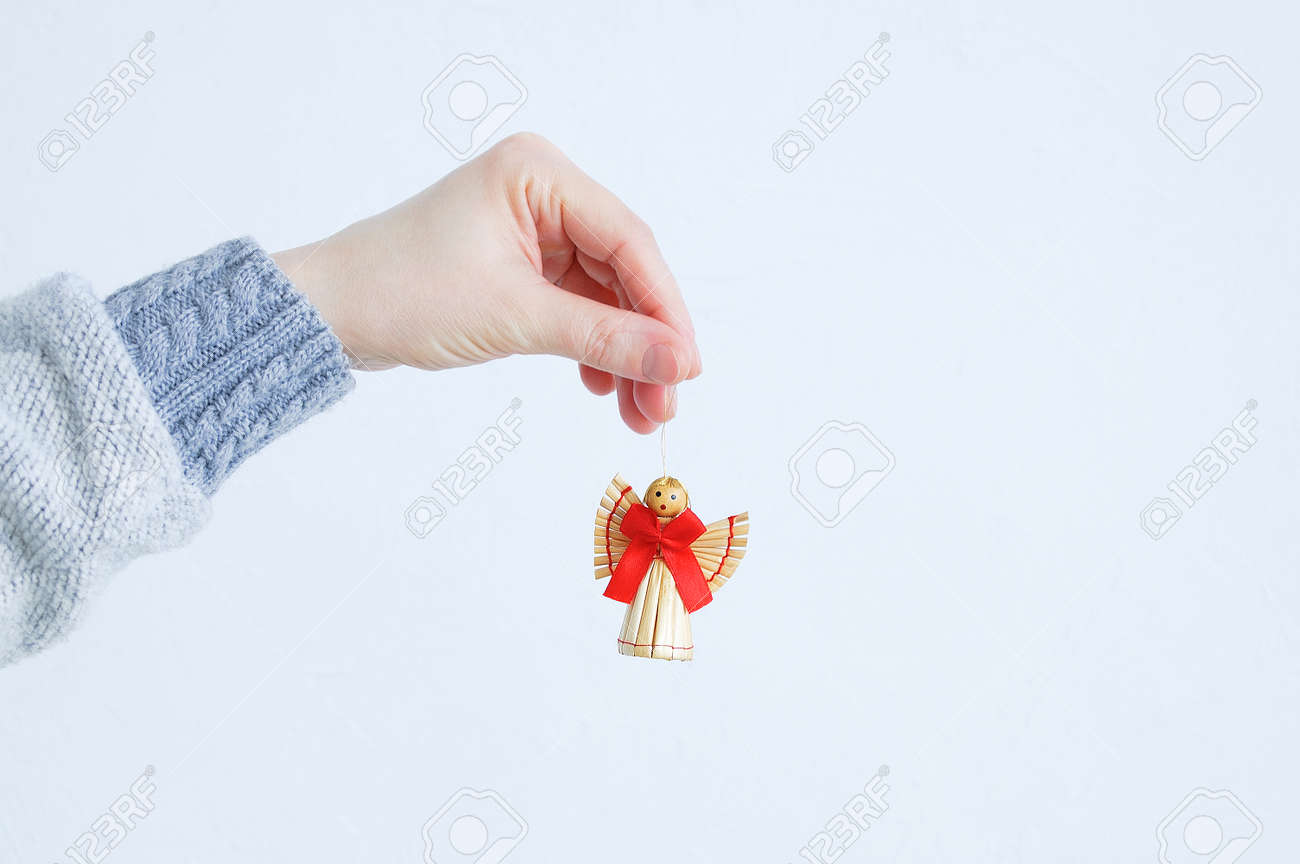 A straw angel hanging in the hand of a Caucasian woman. White background. - 171610483