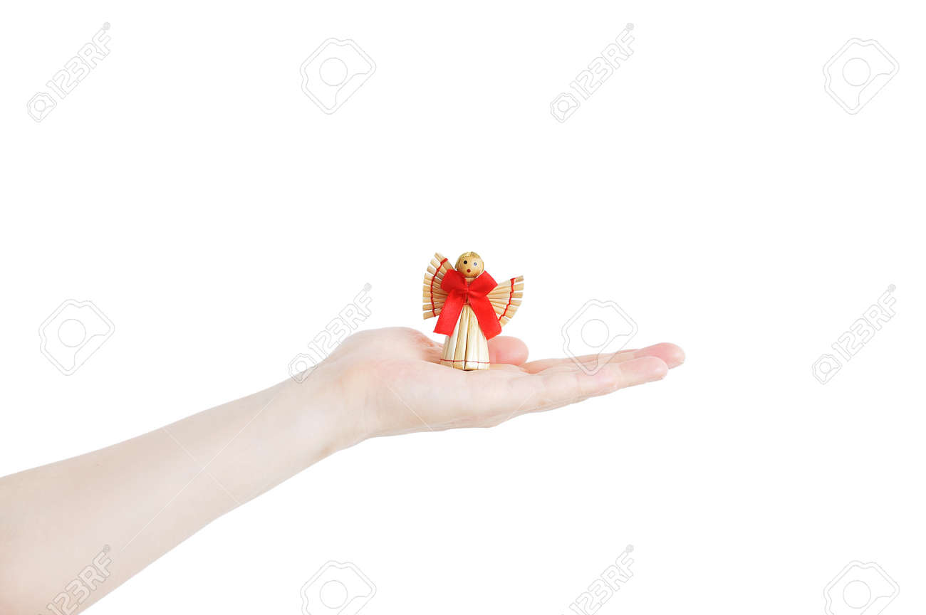 A straw angel with a red bow on the palm of a Caucasian woman. White isolate. - 171610485