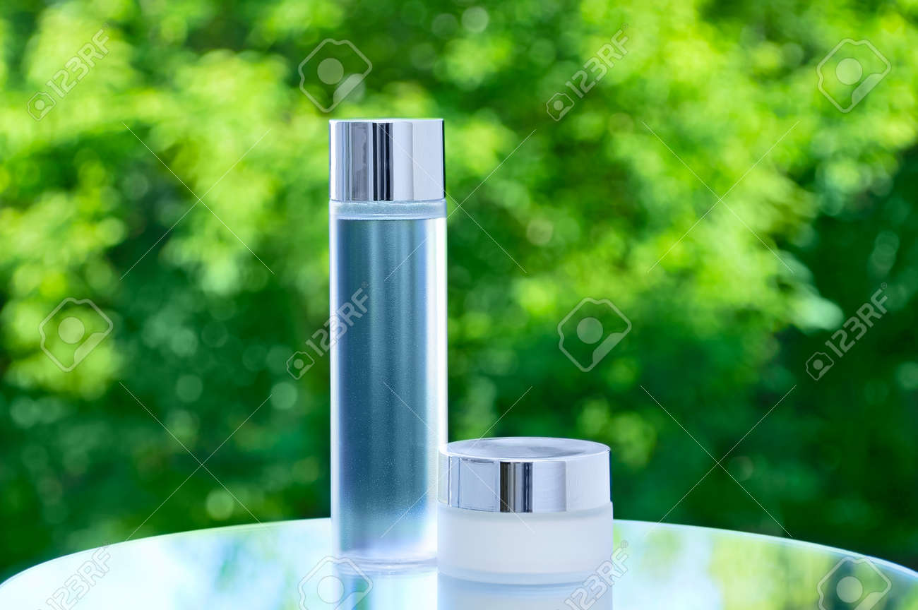Face cream in a glass jar and lotion in a transparent bottle on a mirrored tabletop against a background of green foliage. - 172232559