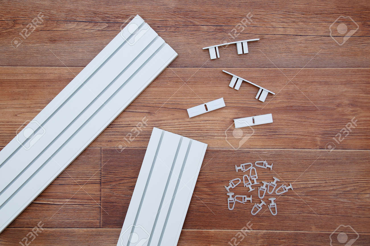White plastic ceiling curtain rod with assembly hardware and hooks. On a brown wooden background. - 172232568