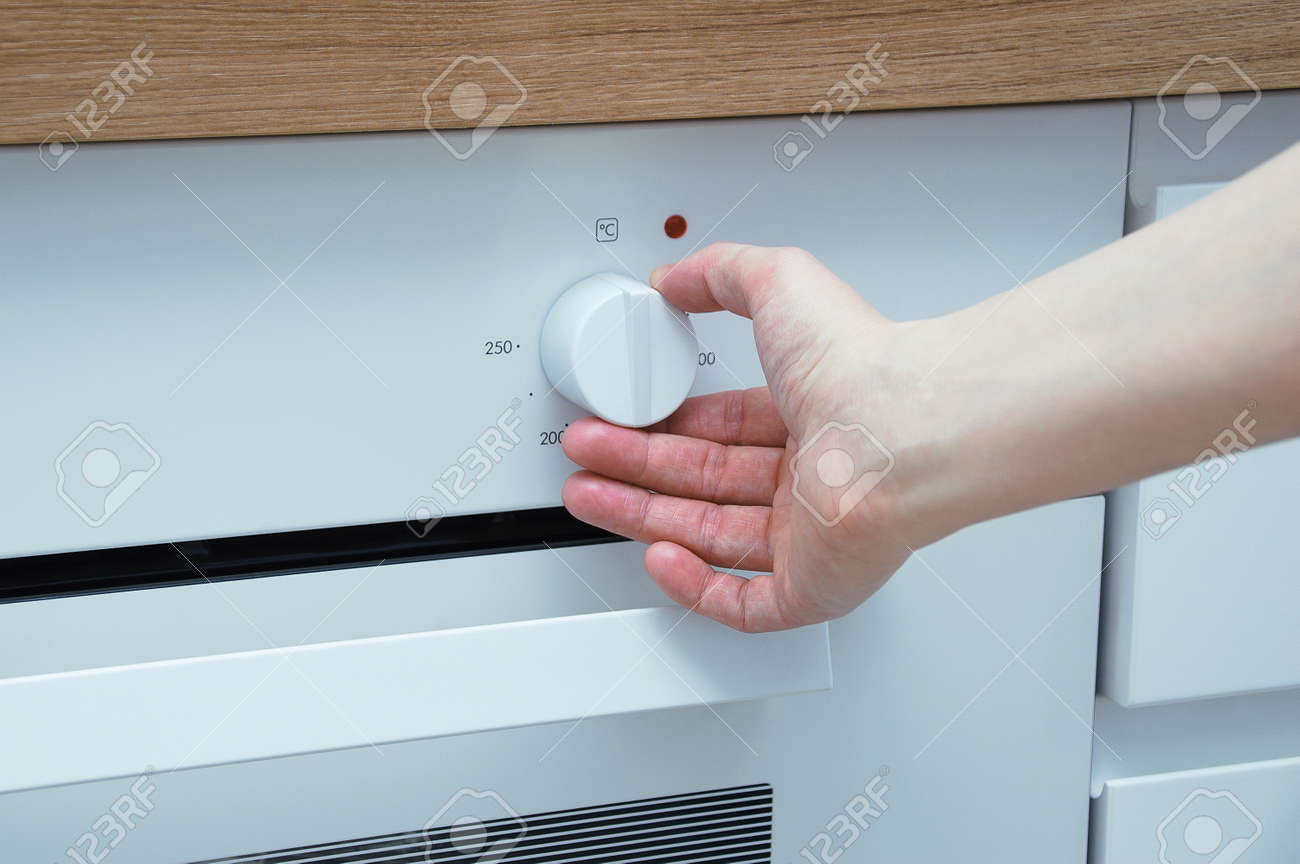 Switch for the built-in cooker. Caucasian woman hand switches the regulator. - 172551754