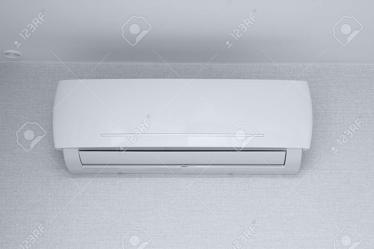 Air conditioner on the wall in the room against the background of white wallpaper. - 172552069