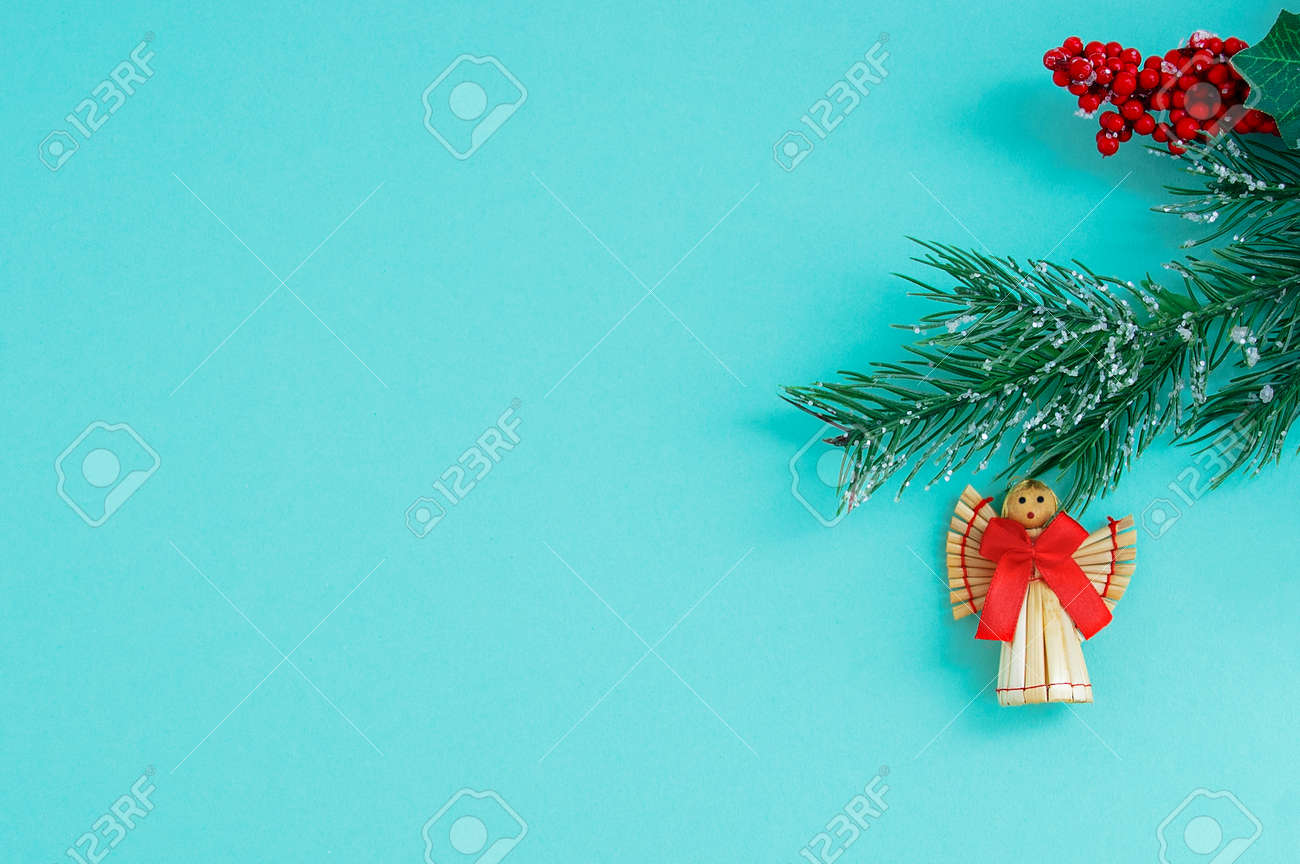 Christmas straw angel with a red bow on a branch of a Christmas tree. Turquoise background. - 172754854