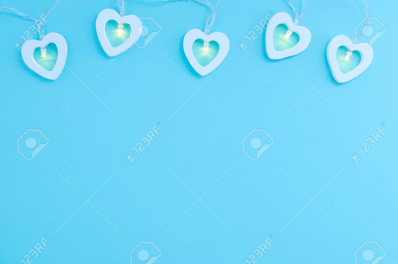 Electric white garland with glowing lights in the form of hearts on a blue background. Place for your text. - 172754908