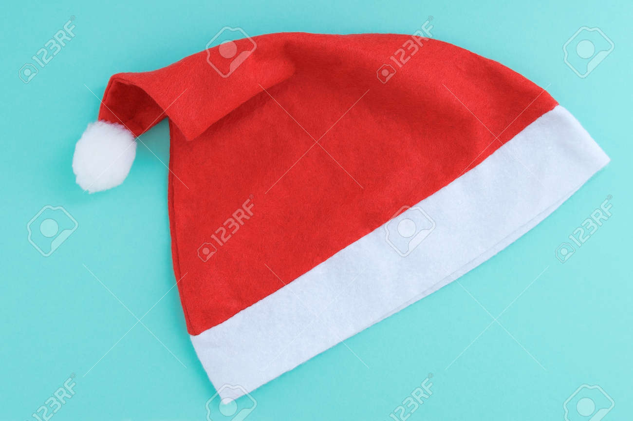 Red santa hat on a turquoise background close-up. - 172808311
