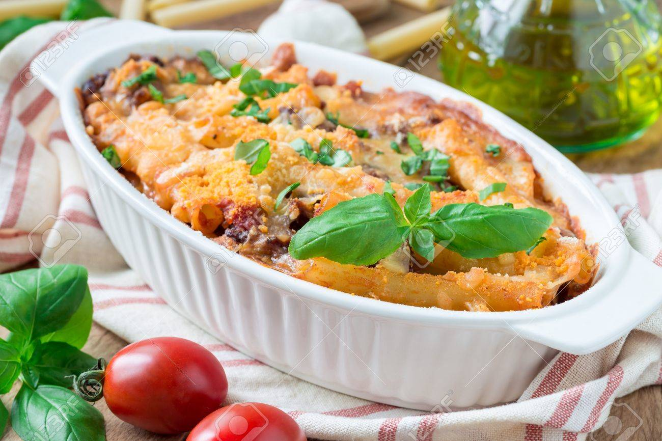 Ziti bolognese in baking dish, pasta casserole with minced meat, tomato sauce and cheese, horizontal - 81597426