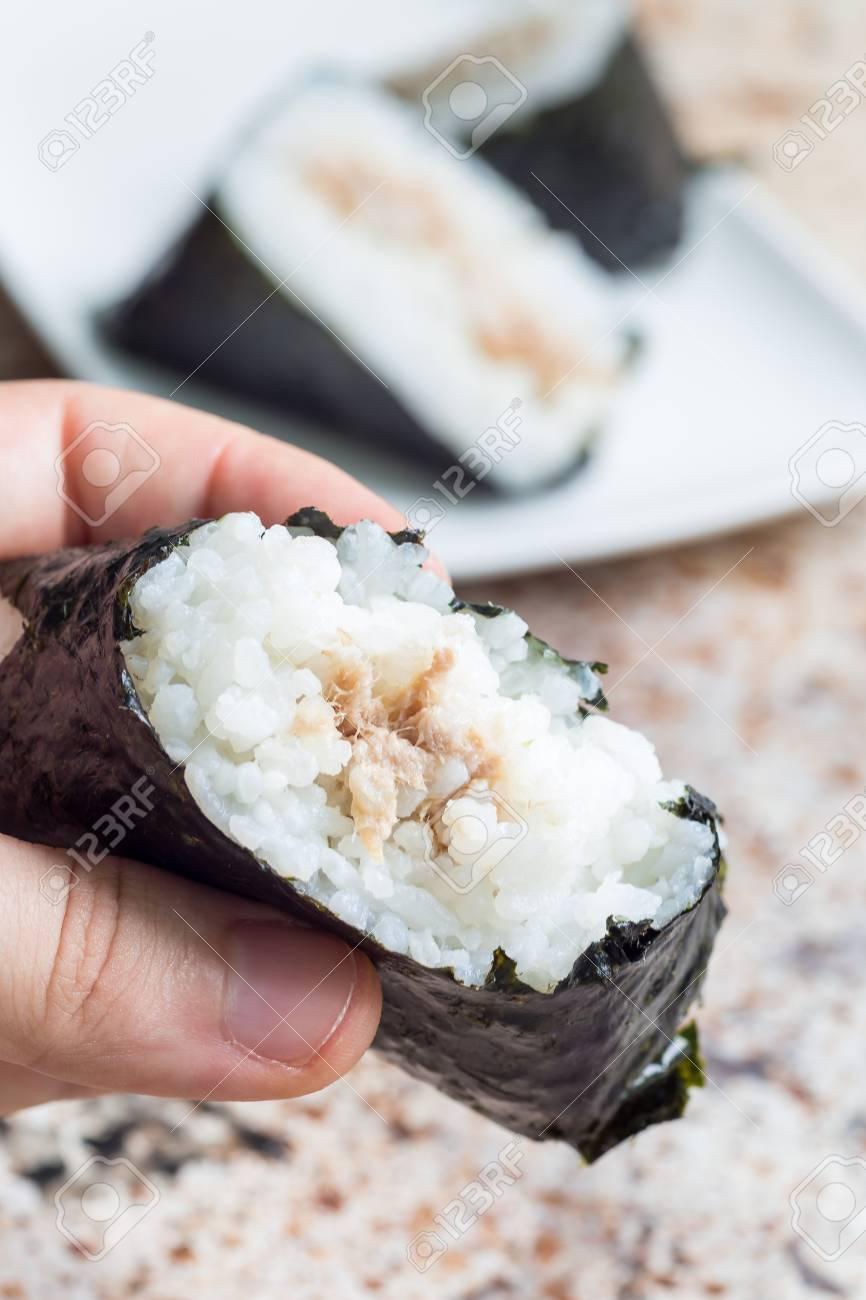 Eating korean triangle kimbap Samgak made with nori, rice and