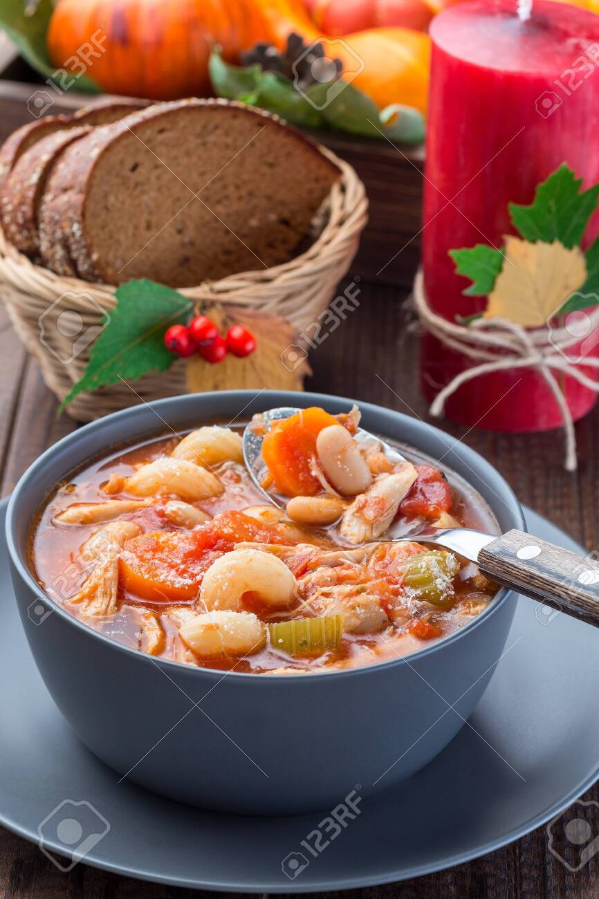 Soup with turkey, pasta, carrot, celery, tomato and cannellini beans, garnished with parmesan cheese, on the table with autumn decoration, reflecting the US Thanksgiving harvest feast, vertical, closeup - 131826969