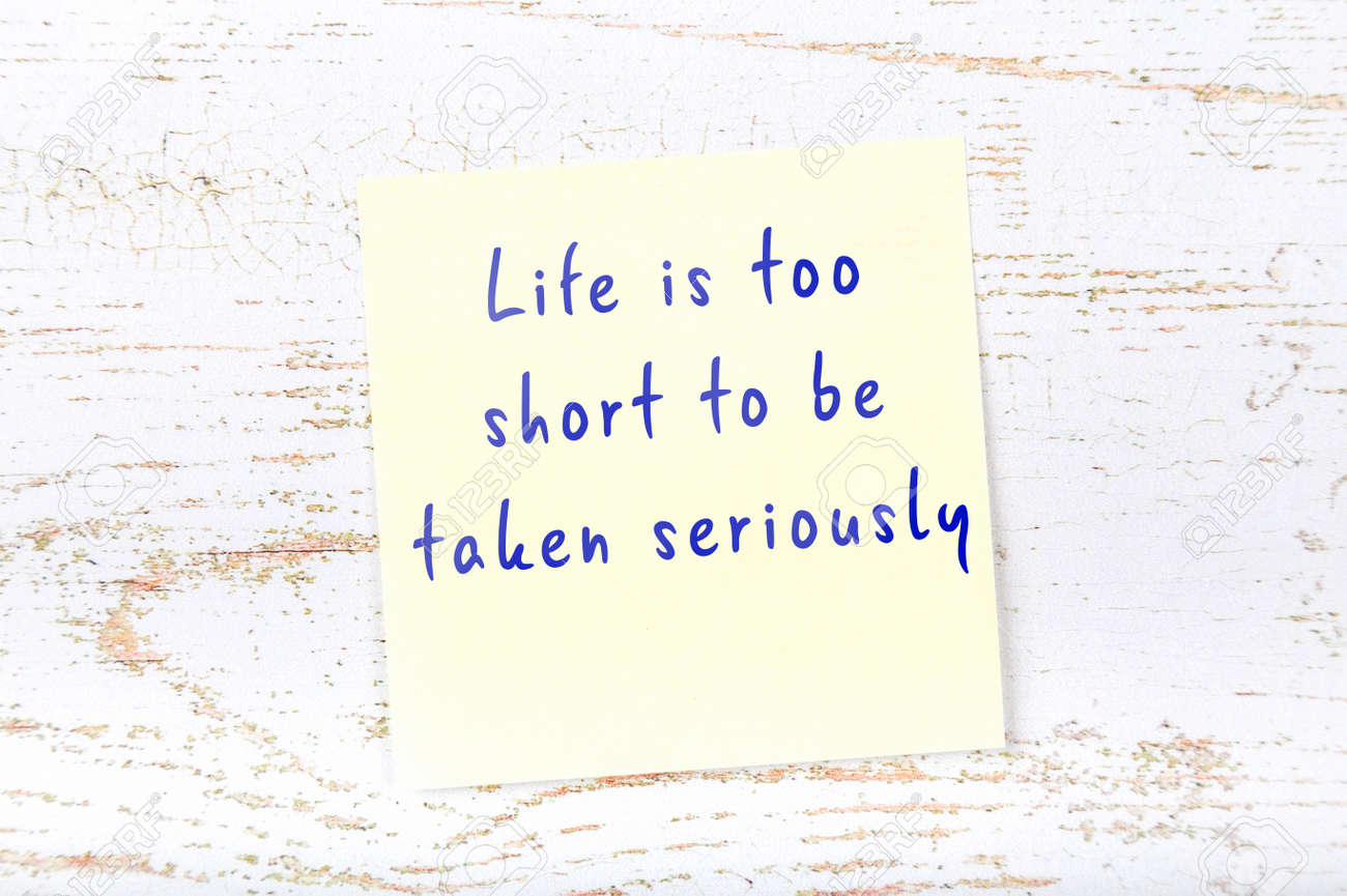 Yellow sticky note with smart quotation handwritten on it hanging on wooden wall - 145485387