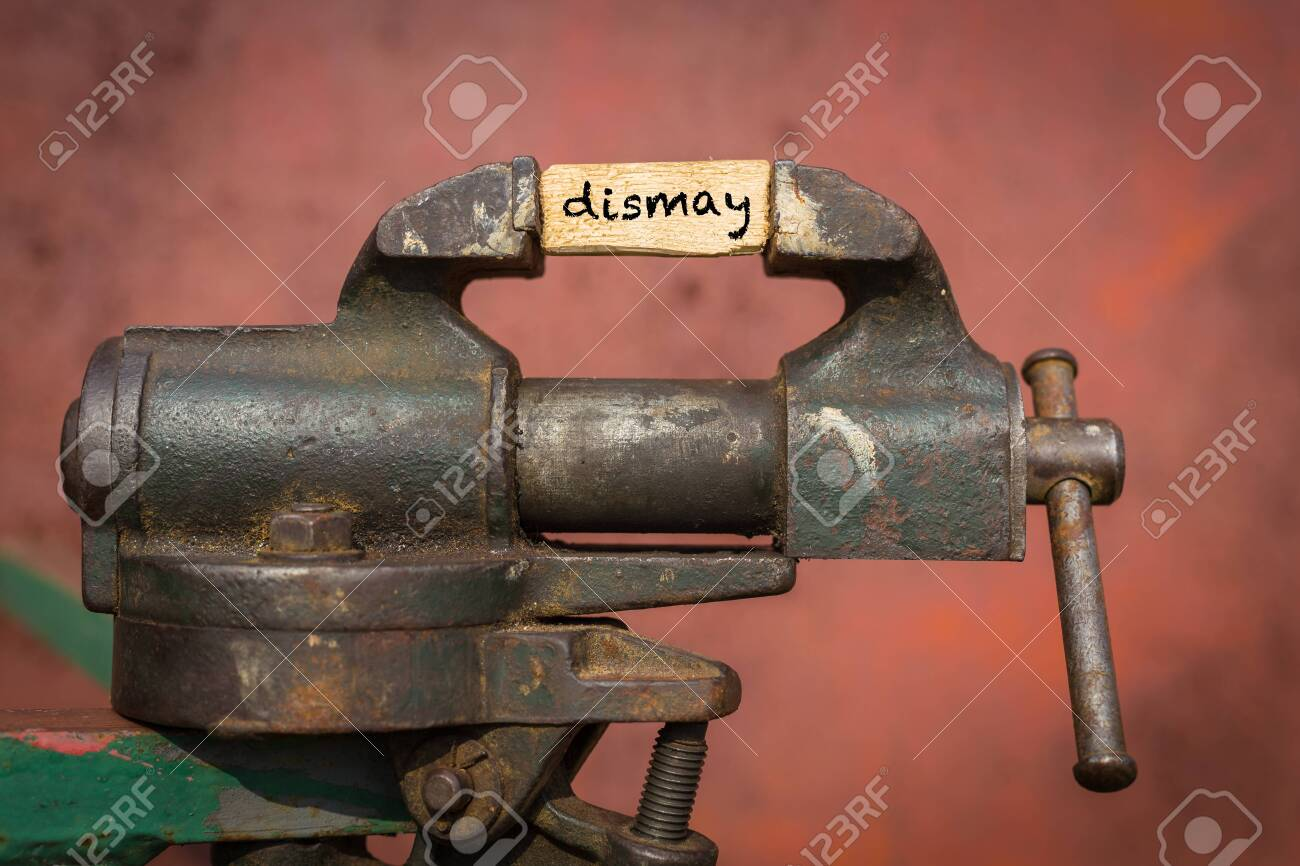 Concept of dealing with problem. Vice grip tool squeezing a plank with the word dismay - 148024146