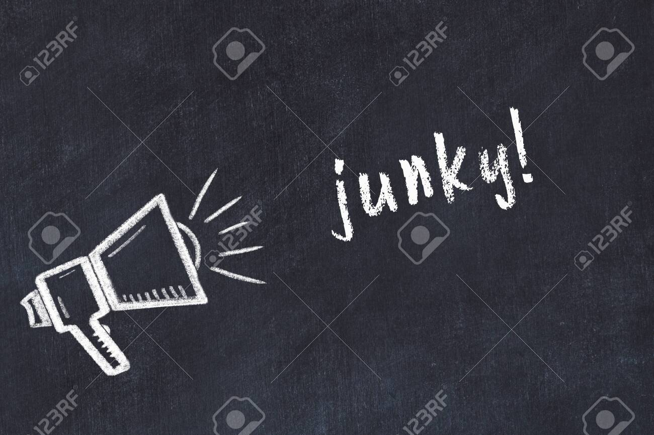 Chalk drawing of loudspeaker and handwritten inscription junky on black desk - 148598856