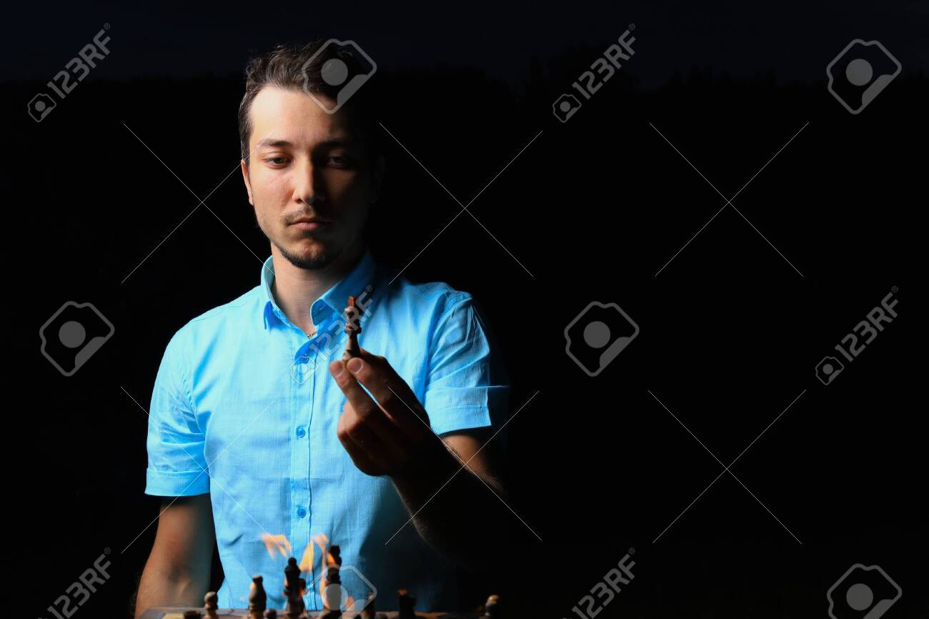 White Caucasian young man or adult guy and a burning chessboard. Dark low key, black background, selective focus. - 152398153
