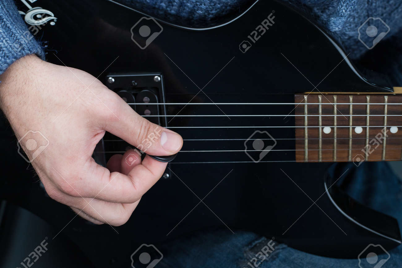 Hands of a guitarist with an electric guitar pick. Abstract music background - 167451667