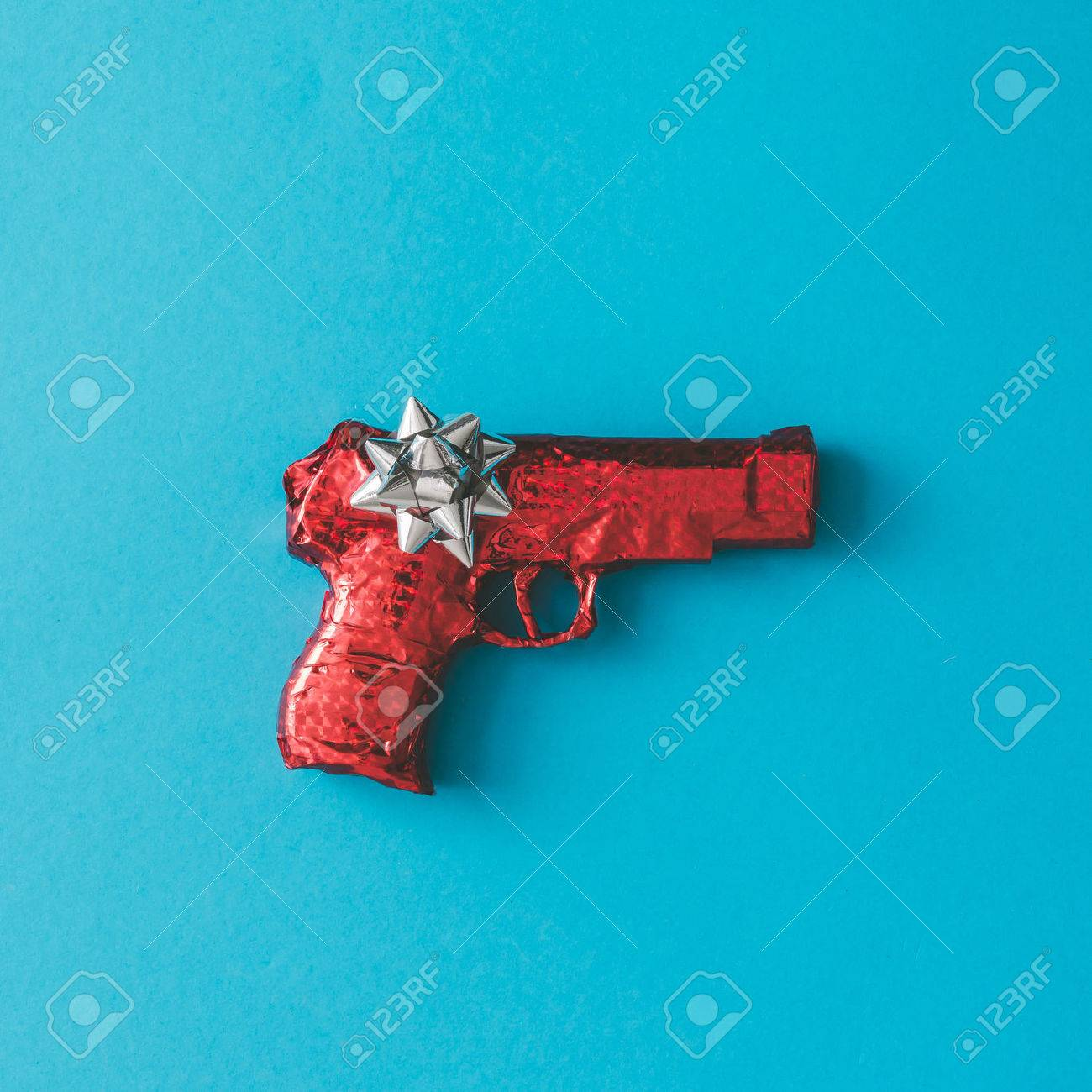 Gun wrapped in red paper with bow on blue background. Flat lay Christmas concept. - 68074981