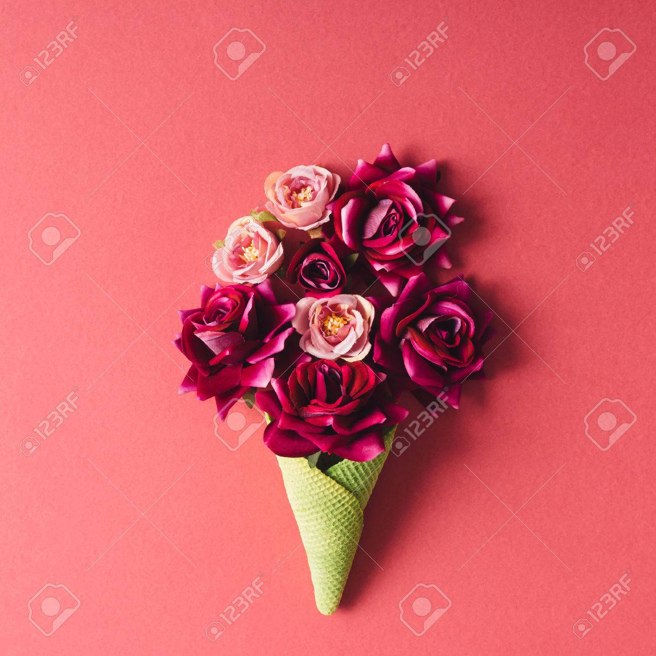 Purple Flowers And Green Icecream Cone On Pink Background Flat Lay Stock Photo