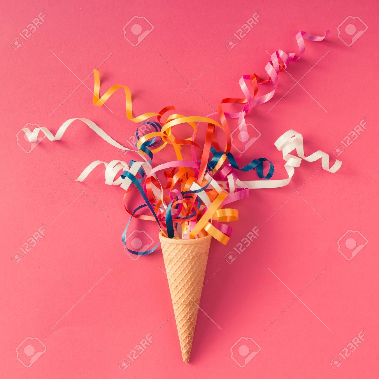 Ice cream cone with colorful party streamers on pink background. Flat lay - 71523109