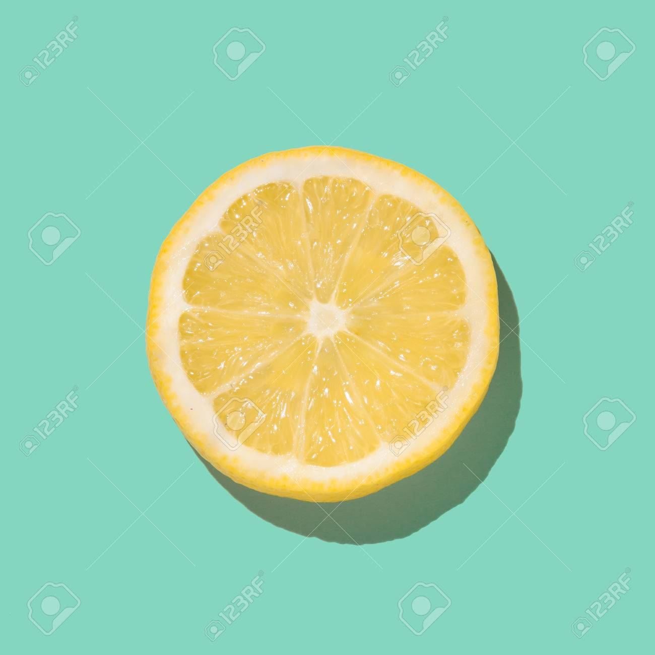 Fresh lemon slice close up on bright blue background. Flat lay. Summer concept. - 82877718
