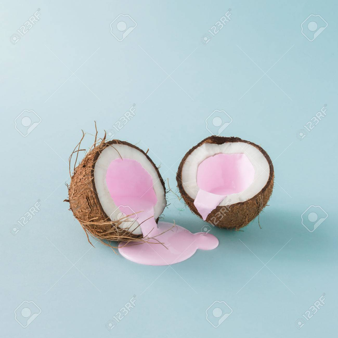 Coconut cracked in half with pink milk pouring. Minimalism. Food creative concept. - 82877726