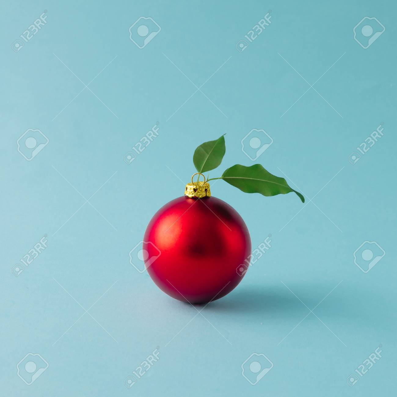 Apple made of red Christmas bauble and leaves on blue background. Christmas food concept. - 90238203