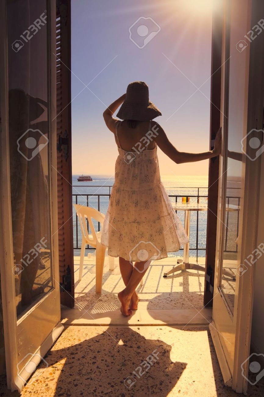 A young woman seen from the back gazing at the sea on the balcony of a hotel Stock Photo - 17991834