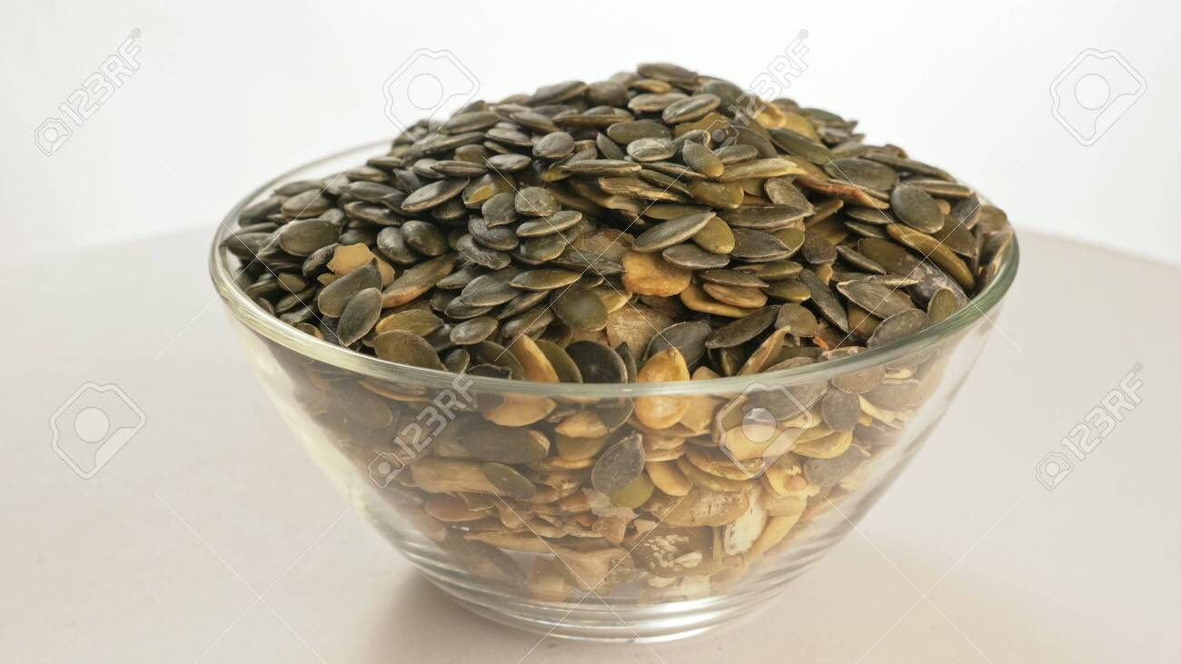 Nuts peeled pumpkin seed rotate are on a table in a plate. Snack in transparent dish on an isolated white background are spinning moving. Delicious and healthy protein-rich diet food. - 135288101