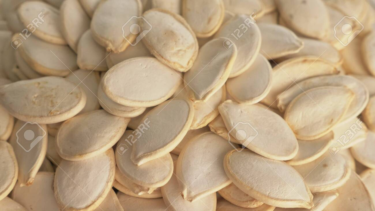 Nuts unpeeled pumpkin seed rotate are on a table in a plate. Snack in transparent dish on an isolated white background are spinning moving. Delicious and healthy protein-rich diet food. - 135448950